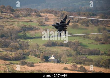 F-15 Eagle, USAF Mc Donnell Douglas low-level fighter jet flying from Valley Anglesey through the Mach Loop in Cadair Idris Wales - Stock Photo