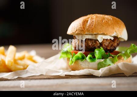 homemade burger and french fries on a wooden plate - Stock Photo