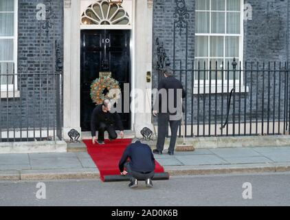 Staff prepare the red carpet outside 10 Downing Street, London, ahead of the arrival of Nato leaders who are gathering to mark 70 years of the alliance. - Stock Photo