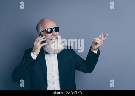 Close-up portrait of his he nice attractive chic classy trendy cheerful cheery, gray-haired man wearing tux specs calling roaming home isolated over d