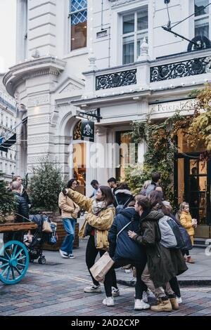 London, UK - November 24, 2019: Young people taking selfie in front of Petersham Nurseries in Covent Garden, London. Covent Garden is a famous tourist - Stock Photo