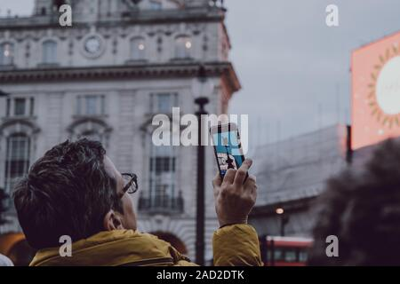 London, UK - November 24, 2019: Rear view of a woman taking a photo on a smart phone of Eros statue in Piccadilly Circus, one of the most popular tour - Stock Photo