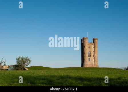 Broadway tower, an 18th century folly in the Cotswolds with a blue sky background and lush green foreground. - Stock Photo