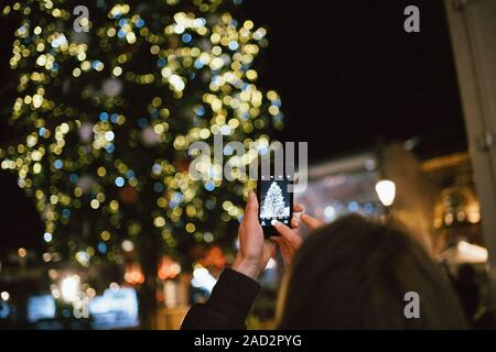 Strasbourg, France - Nov 23, 2017: Rear view of adult woman rising smartphone to take a photograph the illuminated and decorated Christmas Market fir tree - Stock Photo