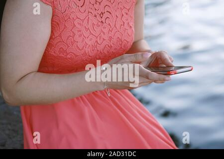 unrecognizable young woman sitting by the water using her smartphone or mobile phone - Stock Photo