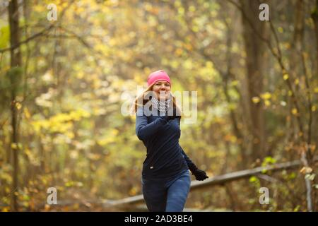 Beautiful sporty young woman jogging in autumn forest - Stock Photo
