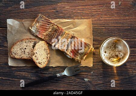 Fish on a paper, bread and glass of beer on old wooden table, top view - Stock Photo