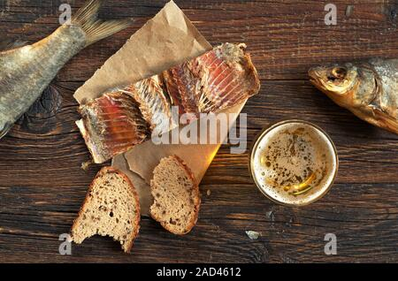 Glass of beer, salted fish and bread on old wooden table, top view - Stock Photo
