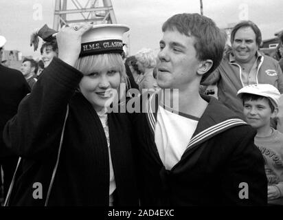 AJAXNETPHOTO. 19TH JUNE, 1982 - PORTSMOUTH, ENGLAND. - FALKLANDS VETERAN - A SAILOR OF THE SHEFFIELD CLASS (TYPE 42/1&2) DESTROYER HMS GLASGOW LOSES HIS HAT TO A PRETTY YOUNG RELATIVE WHEN HIS BOMB DAMAGED SHIP RETURNED TO PORTSMOUTH IN 1982.  PHOTO:JONATHAN EASTLAND/AJAX.  REF:HD NA GLAS 82_16. - Stock Photo