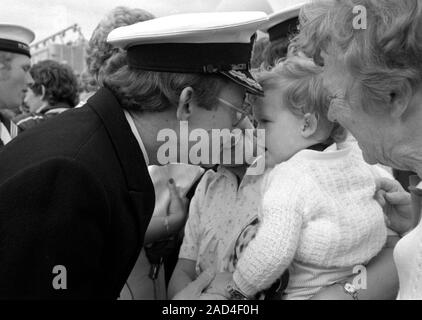 AJAXNETPHOTO. 19TH JUNE, 1982.PORTSMOUTH, ENGLAND. - FALKLANDS VETERAN - AN OFFICER OF THE SHEFFIELD CLASS (TYPE 42/1&2) DESTROYER HMS GLASGOW RECEIVES A WARM WELCOME FROM HIS YOUNG FAMILY WHEN HIS BOMB DAMAGED SHIP RETURNED TO PORTSMOUTH IN 1982.  PHOTO:JONATHAN EASTLAND/AJAX.  REF:HD NA GLAS 82_22. - Stock Photo