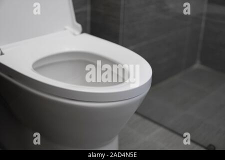 White toilet in modern home. White toilet bowl in bathroom. - Stock Photo