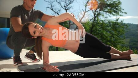 Couple Doing Stretching Exercises Together in front of luxury villa - Stock Photo