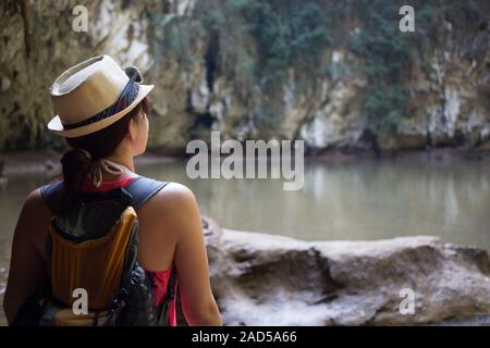 Brunette in hat among mountains - Stock Photo
