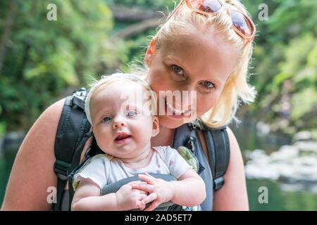 Happy, smiling mother carrying baby child in sling, ergonomic baby carrier. Walking outdoors in nature during summer. - Stock Photo