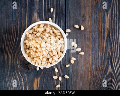 Top view of white cups, bowls with a handful of pine nut, cedar nuts on a wooden background - Stock Photo