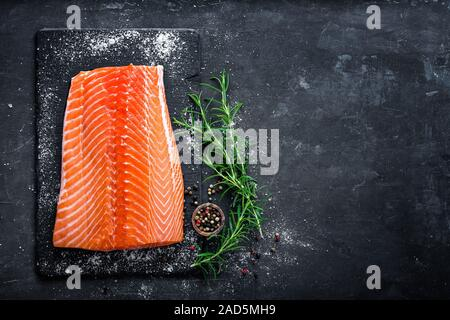 Raw salmon filet on dark slate background, wild atlantic fish - Stock Photo