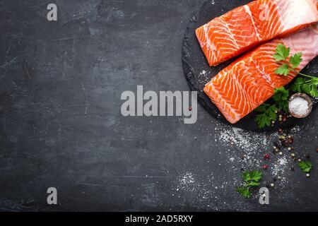 Raw salmon fish fillet on black background - Stock Photo