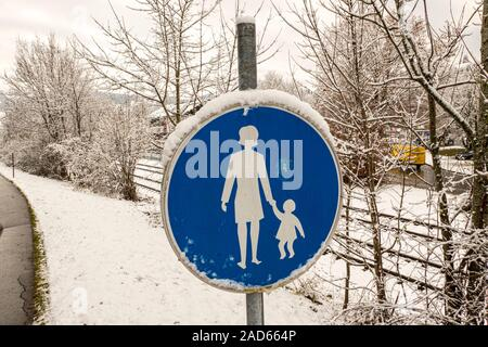 Pedestrian sign in blue in the snow in the city - Stock Photo