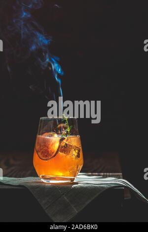 Pink cocktail with fig, thyme and ice in glass with smoke on dark wooden background, close up. Sunny light. Summer drinks and alcoholic cocktails. Alc - Stock Photo