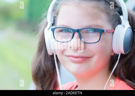 Cute girl listening to music with headphones outdoor in front of the car - Stock Photo