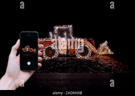 Mobile picture of a Blurred wheel loader decorated with lights at christmas - Stock Photo