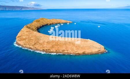 Molokini Crater, aerial shot of the Maui side of the crescent shaped islet with Kahoolawe and Lanai in the distance, Maui, Hawaii. - Stock Photo