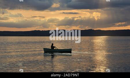 Summer sunset in Ebeltoft, Denmark. Man rowing in a small boat. - Stock Photo