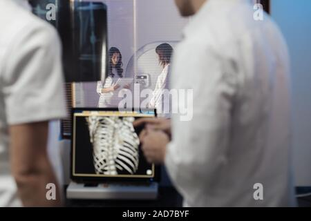 In Control Room Doctor and Radiologist Discuss Diagnosis while Watching Procedure, In the Background Patient Undergoes MRI or CT Scan Procedure. - Stock Photo