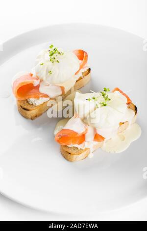 Bruschetta with salmon and poached egg. - Stock Photo