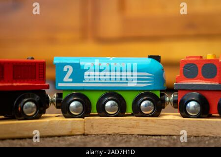 A close up of a child's wooden magnetic train set on a wooden track - Stock Photo