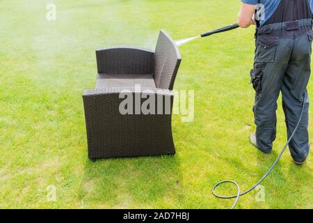 power washing garden furniture - made of rattan - Stock Photo