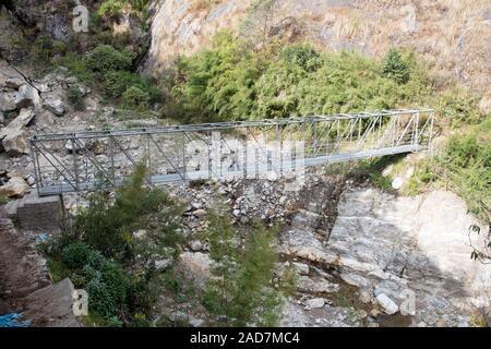 Solid footbridge across small stream near, Amjilosa, Taplejung District, Nepal - Stock Photo