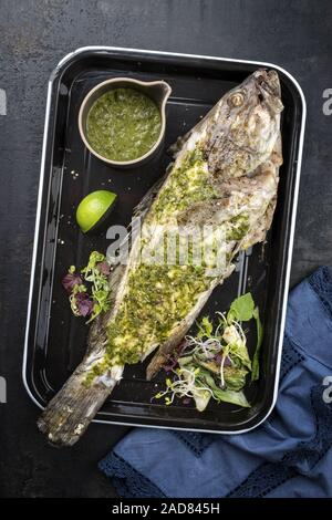 Barbecue white grouper with chimichurri sauce aji criollo as top view in a black skillet - Stock Photo