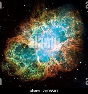 This is a mosaic image, one of the largest ever taken by NASA's Hubble Space Telescope of the Crab Nebula, a six-light-year-wide expanding remnant of a star's supernova explosion. Japanese and Chinese astronomers recorded this violent event nearly 1,000 years ago in 1054, as did, almost certainly, Native Americans.   The orange filaments are the tattered remains of the star and consist mostly of hydrogen. The rapidly spinning neutron star embedded in the center of the nebula is the dynamo powering the nebula's eerie interior bluish glow. The blue light comes from electrons whirling at nearly t - Stock Photo