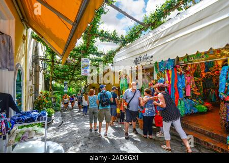 Tourists walk the narrow shaded path past cafes, shops and boutiques at the hillside village of Positano, Italy on the Amalfi Coast - Stock Photo