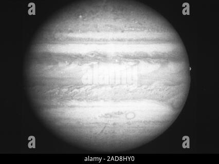 This black and white picture of Jupiter, taken in green light at 1:14 a.m. on the 11th March, 1991 by the Planetary Camera on NASA's Hubble Space Telescope, shows a wealth of fine detail in the clouds that cover the planet. The Great Red Spot is seen at the lower right, also on the right near the equator the satellite Europa is disappearing behind the limb of the planet. The dark 'j' shaped clouds along the equator are the result of a pattern of intense jet streams in the Jovian atmosphere. This picture is as sharp as the Voyager pictures taken five days before the closest approach in 1979. - Stock Photo