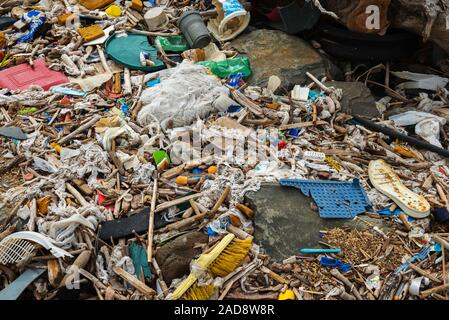Spilled garbage on the beach near the big city. Empty used dirty plastic bottles and other garbage. - Stock Photo