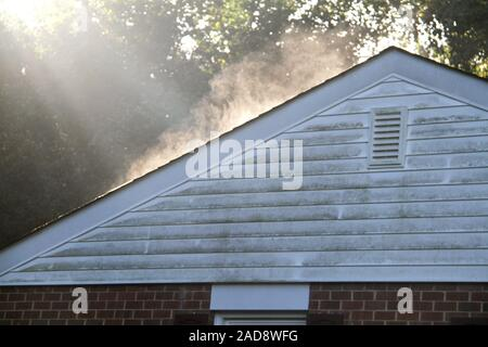 Vapors coming out of a house roof after rain. - Stock Photo