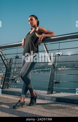 Attractive woman on the bridge next to the banister stock photo - Stock Photo