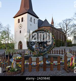 fountain decorated for Easter and St. Petri Church of Huesten, Arnsberg, Germany Europe - Stock Photo