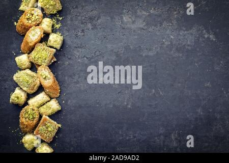 Traditional Oriental baklava collection as top view on a black board with copy space right - Stock Photo