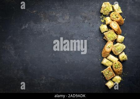 Traditional Oriental baklava collection as top view on a black board with copy space left - Stock Photo