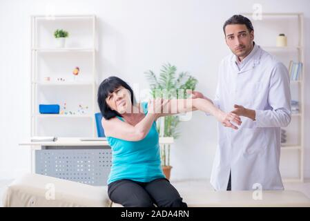 Young male doctor examining old female patient - Stock Photo