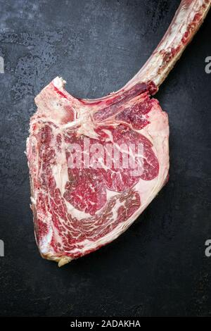 Traditional raw dry aged wagyu tomahawk steak as top view on an old rustic board - Stock Photo
