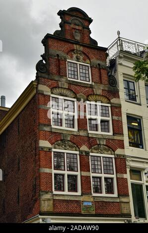 Amsterdam, Holland, August 201. In Dam Square, a typical historic red brick house. Narrow and high with white glass frames. - Stock Photo