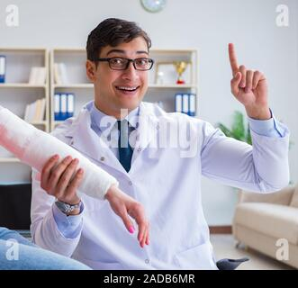 Doctor and patient during check-up for injury in hospital - Stock Photo