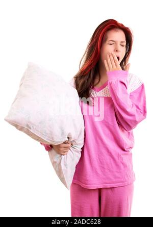 Portrait of tired young girl in pajamas holding a white pillow and yawning, with closed eyes and covering her open mouth with her palm, isolated. - Stock Photo