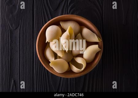 Top view of conchiglie pasta in bowl on black wooden table - Stock Photo