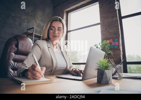 Low below angle view photo of serious concentrated woman noting comparing data on laptop with data in notebook