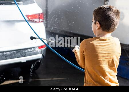 Little kid cleaning a car with a high pressure hose